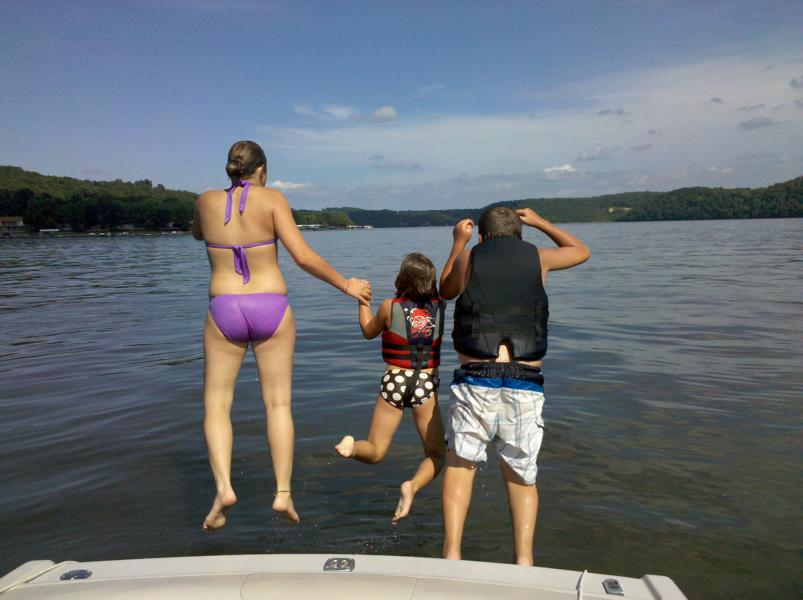 Kids jumping off boat into Lake of the Ozarks